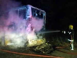Bombeiros tentando apagar as chamas no ônibus